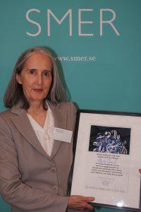 Marie Chenik håller i prisdiplomet
